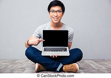 Smiling asian man showing finger on laptop screen - Smiling...