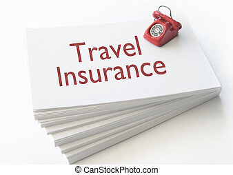 Travel insurance - Small telephone on top of a stack of...