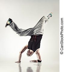 Young man modern dance. Soft yellow background.