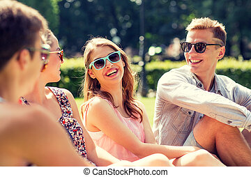 group of smiling friends outdoors sitting in park -...