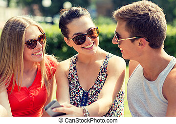 smiling friends with smartphone sitting in park -...