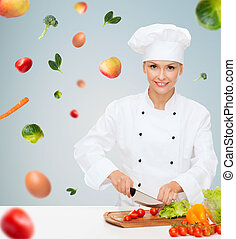 smiling female chef chopping vegetables