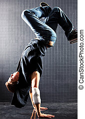 Young man modern dance On dark wall background