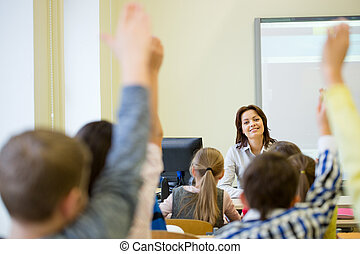 group of school kids raising hands in classroom