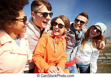 smiling friends in sunglasses laughing on street - tourism,...