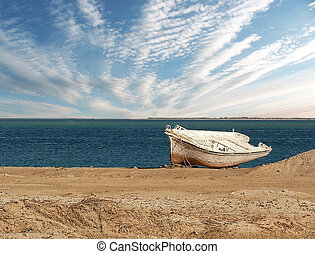lonely fishing boat lies on the shore during ebb against the...