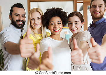 happy creative team showing thumbs up in office - business,...