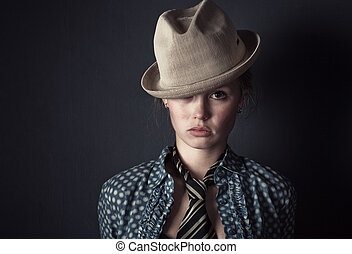 Woman in hat and tie portrait. On dark wall background.