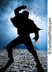 Dancing man silhouette. Bright light flash behind.