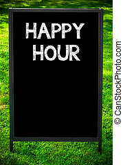 HAPPY HOUR message on sidewalk blackboard sign against green...