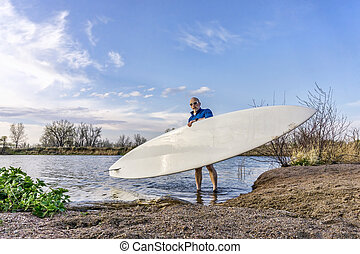 launching stand up paddleboard - senior male paddler is...