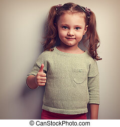 Smiling girl showing thumb up sign and looking happy. Vintage portrait