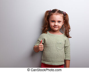 Happy girl showing thumb up sign on blue background