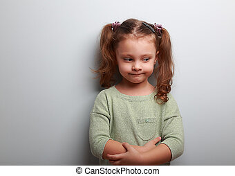 Fun thinking kid girl looking on blue wall background....