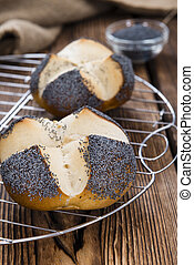 Homemade Pretzel Roll (with Poppyseed) on rustic wooden...