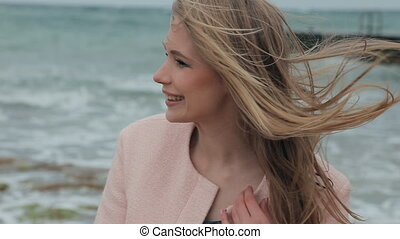 Beautiful blonde smiling optimistic during a storm near the...