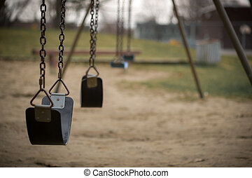 Empty Swings at Playground on Dull Day - Children's swings...