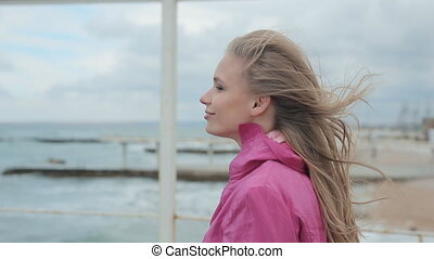 The girl in a coat walking on the pier during a storm