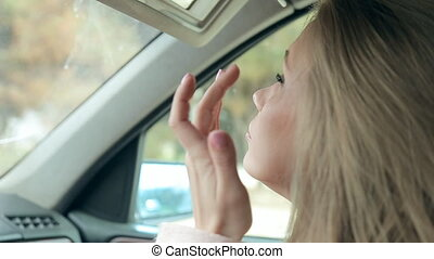 Sensual woman looking in rear view mirror and putting make up in car