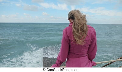 Girl in a pink coat walking on the pier stands during a storm at sea and looking