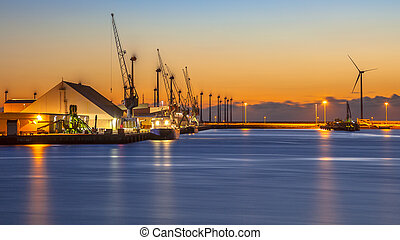 Industrial harbor night scene - Boats on a wharf in an...