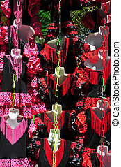 typical dot-patterned flamenco dresses on sale in a street...