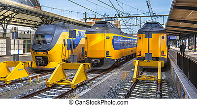 Three Fast Intercity Commuter Trains waiting at a station -...
