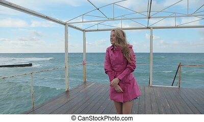 The girl in a coat walking on the pier during a storm - The...