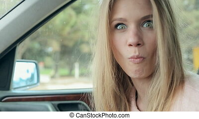 Shocked woman in a car - Cute blonde sitting in a car and...
