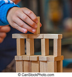Hand putting Wood Building Block on a Constuction - Boy...