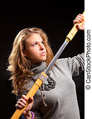 Young woman with samurai sword On dark background