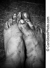 Dirty male worker foots. Black and white contrast colors.