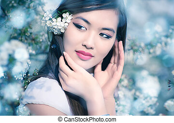 Young woman with cherry flowers. Soft blue tint.