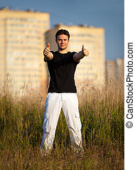 Young man showing success handsign standing at the field on...