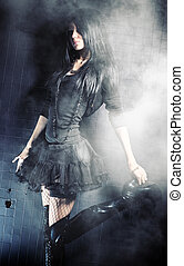 Goth woman fashion. On black wall background.