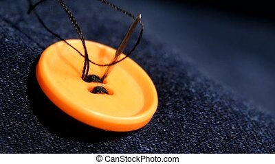 Sewing an orange button on jeans, denim, close up - Sewing...