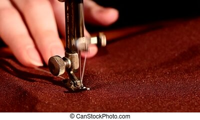 Womans hands behind her sewing process on brown tissue -...