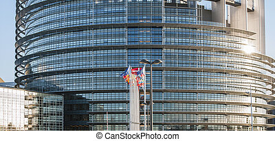 Frontal view of The European Parliament building in Strasbourg, France with flags waving on a spring evening