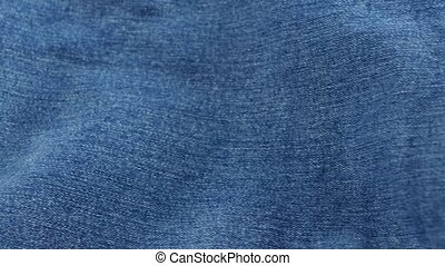 Blue jeans pocket on brown cloth, cam moves to the left,...