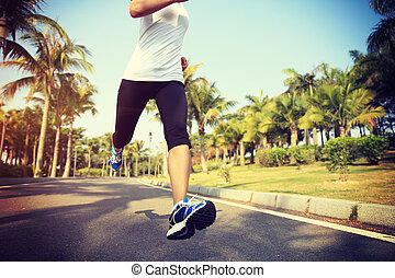 fitness jogger legs running at tropical park. woman fitness...
