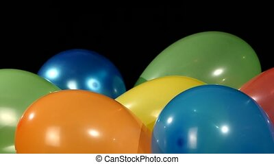 Lot of multicolored balloons, rotation, on black background...