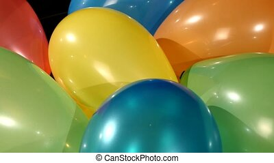 Different multicolored balloons, rotation, on black background, close up