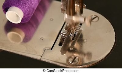 Old working silver sewing machine with purple thread, close...