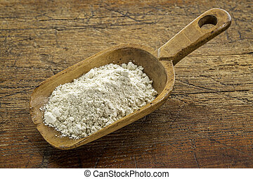 gluten free quinoa flour on a wooden scoop against weathered...