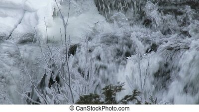 Small waterfall in winter in Canada, with ice and frozen...