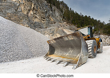 huge shovel of wheel loader at stone quarry with gravel hill