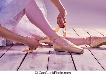 Professional ballerina putting on her ballet shoes -...