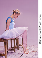 Tired ballet dancer sitting on the wooden floor on a pink...