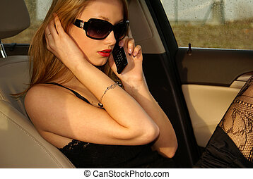 Sexy woman in the car - Sexy woman talking on the phone in...