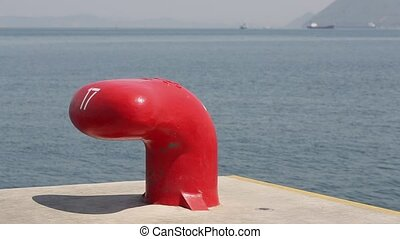 Iron bollard painted in red at the harbor